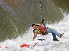 A local construction worker, suspended from a crane, rescues a woman who fell into the Des Moines River near the Center Street Dam in downtown Des Moines, Iowa Tuesday, June 30, 2009. A man who also fell into the water died. (AP Photo/The Des Moines Register, Mary Chind) ** NO SALES, MAGS OUT, MANDATORY CREDIT **